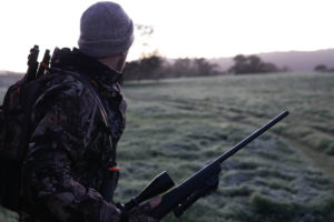 Hunter in field with rifle